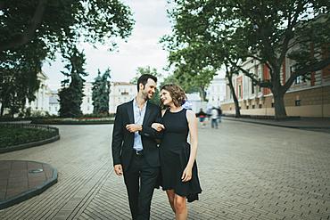 Smiling Caucasian couple walking arm in arm