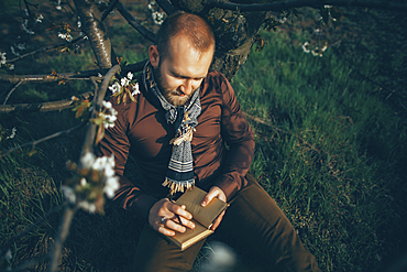 Caucasian man leaning on tree writing in journal