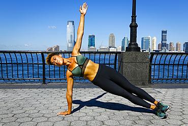 Mixed race woman balancing on arm at waterfront