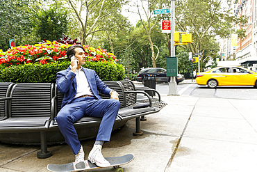Caucasian businessman sitting on bench in city talking on cell phone