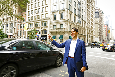 Caucasian businessman standing in street hailing taxi