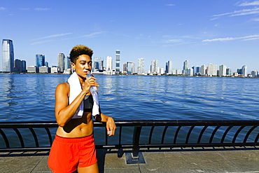 Mixed race woman drinking water from bottle at waterfront