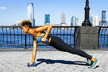 Mixed race woman lifting dumbbells at waterfront