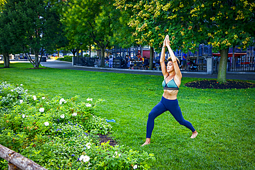 Mixed race woman performing yoga in park