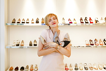Passionate Caucasian woman hugging shoes in store