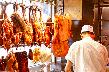 Butcher standing near hanging meat
