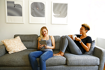 Women drinking coffee and using digital tablet on sofa