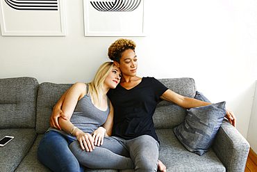 Women cuddling on sofa