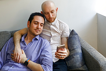 Caucasian men holding hands and texting on cell phone