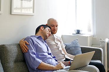 Caucasian men hugging on sofa and using laptop