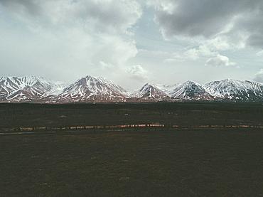 Field near snowy mountain range