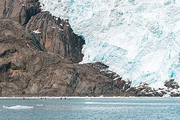 Distant people kayaking near glacier