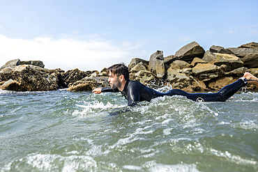 Caucasian man paddling on surfboard