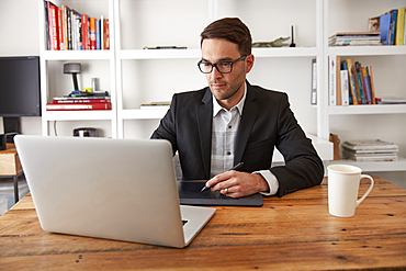 Caucasian businessman using laptop and digital tablet in office