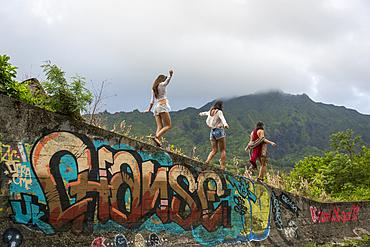 Friends walking on graffiti wall near mountain
