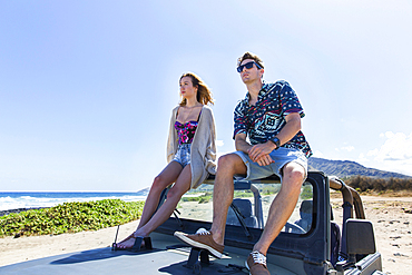Couple sitting on windshield of convertible car on beach