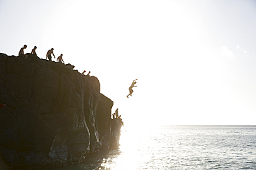 Friends jumping from cliff into ocean