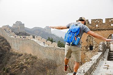 Tourist balancing on Great Wall of China, Beijing, China