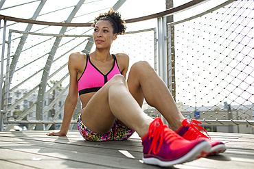 Mixed Race woman sitting on wooden floor near fence