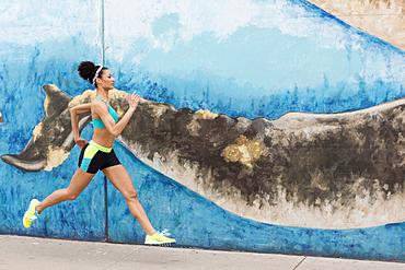 Mixed Race woman running on sidewalk near mural