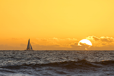Distant sailboat in ocean at sunset