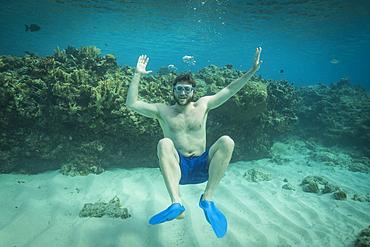 Portrait of smiling man swimming underwater in ocean