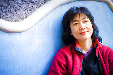 Pensive Japanese woman leaning on wall