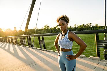 Mixed race woman resting on bridge