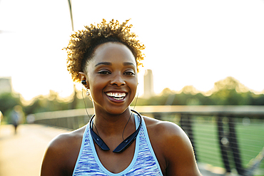 Smiling mixed race woman listening to earbuds on bridge