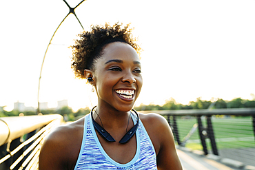 Mixed Race woman listening to earbuds on bridge and laughing