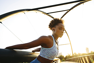 Portrait of mixed race woman stretching arms by pulling on railing