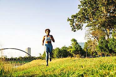 Mixed Race woman running in grass near waterfront