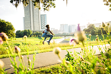 Mixed Race woman jumping on running path in park beyond wildflowers