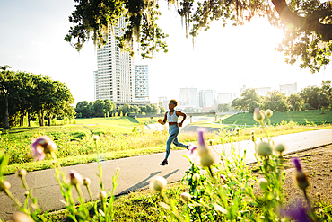 Mixed Race woman running on path in park beyond wildflowers