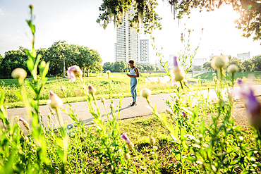 Mixed Race woman standing on running path in park beyond wildflowers