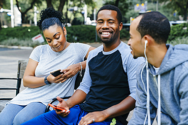 Black friends sitting on bench holding cell phones