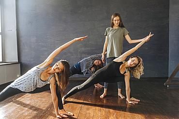 Instructor watching Caucasian women stretching arms in yoga class