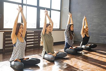 Caucasian women stretching arms in yoga class