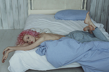 Topless Caucasian woman laying on bed wearing jeans