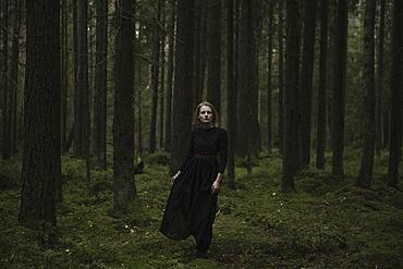 Caucasian woman standing in dark forest