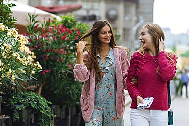 Smiling Caucasian women walking with hands in hair