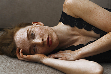 Pensive Caucasian woman with freckles laying on floor