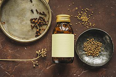 Alternative medicine jar with blank label near seeds