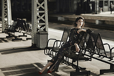 Caucasian woman sitting on bench at train station