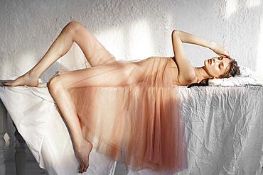 Caucasian woman laying on white sheet
