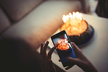 Mixed race girl photographing birthday cake with cell phone