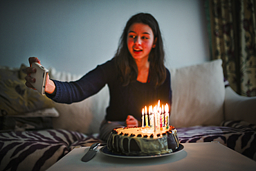 Mixed race girl posing for cell phone selfie with birthday cake