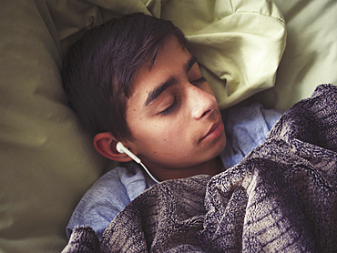Mixed race boy laying in bed listening to earbuds