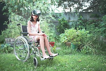 Mixed race girl in wheelchair using virtual reality goggles in backyard