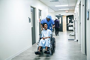 Nurse pushing boy in wheelchair